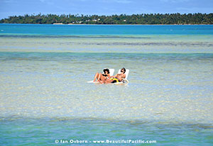 sunbathing in lagoon beside aitutaki village resort
